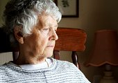 senior woman, eighty years old with sad serious expression staring out of window
