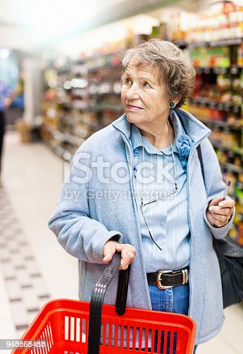 istock Senior woman with shopping basket in supermarket 948868488