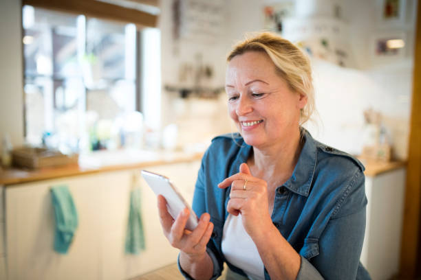 senior woman with smartphone at home sitting in the kitchen - older woman phone stock photos and pictures