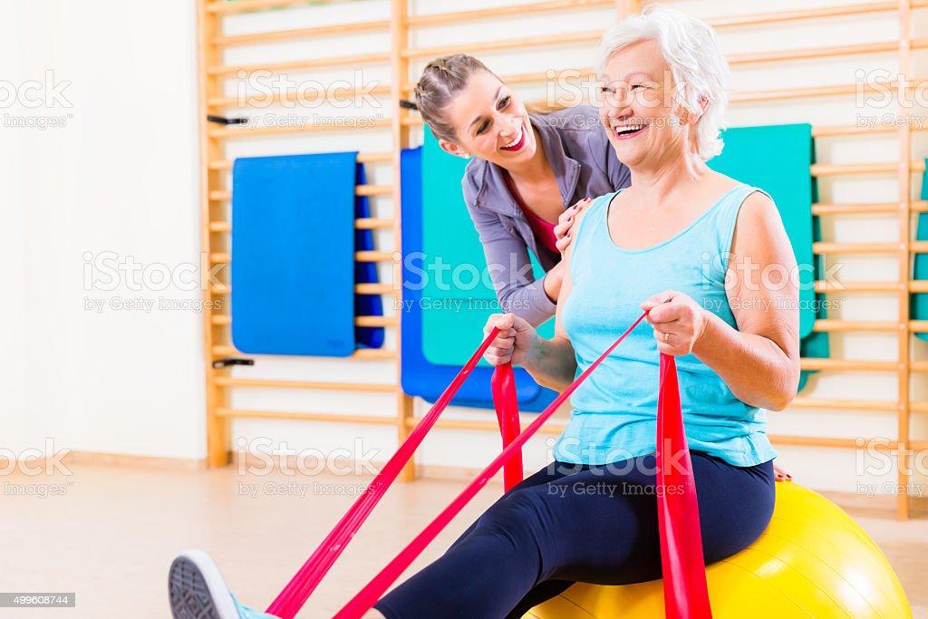 Senior mujer con banda elástica en gimnasio - foto de stock