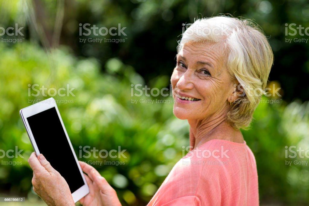 Senior woman with tablet at yard foto stock royalty-free