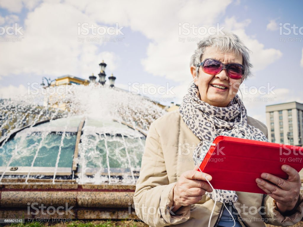 Senior woman with tablet in downtown of Moscow stock photo