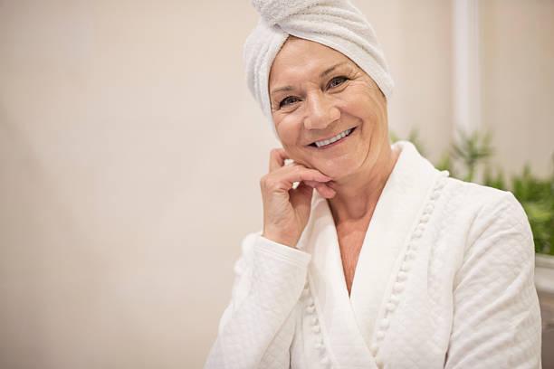 senior donna con asciugamano per i capelli - lavarsi i capelli foto e immagini stock