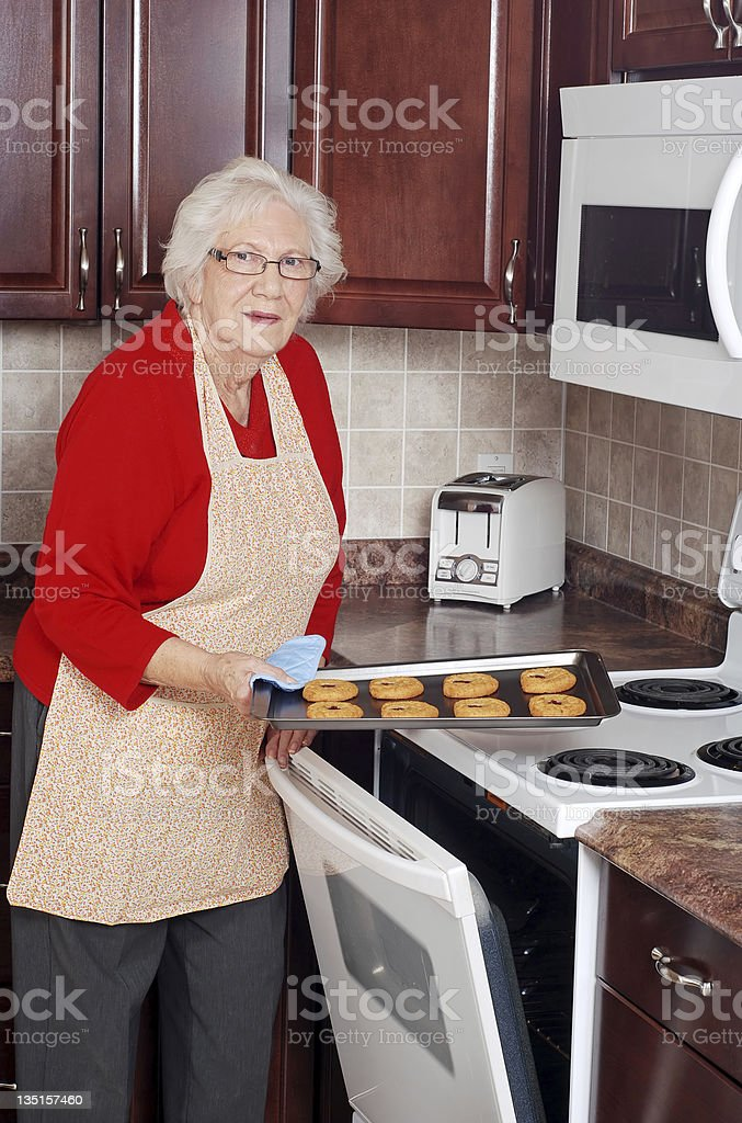 senior woman with tray of fresh baked cookies royalty-free stock photo
