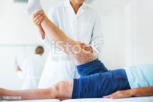 Closeup side view of  female doctor massaging legs and calves of a senior female patient with visible varicose veins on both legs. Both patient and doctor are recognizable.