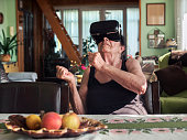 istock Senior woman with VR headset or 3d glasses playing videogame at home 1338300060