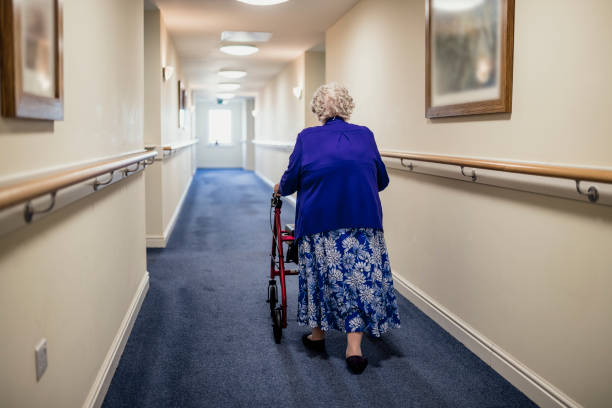 Senior Woman with Walker in a Care Home A senior woman walking down a corridor with the assistance of a walker. view from rear aging stock pictures, royalty-free photos & images