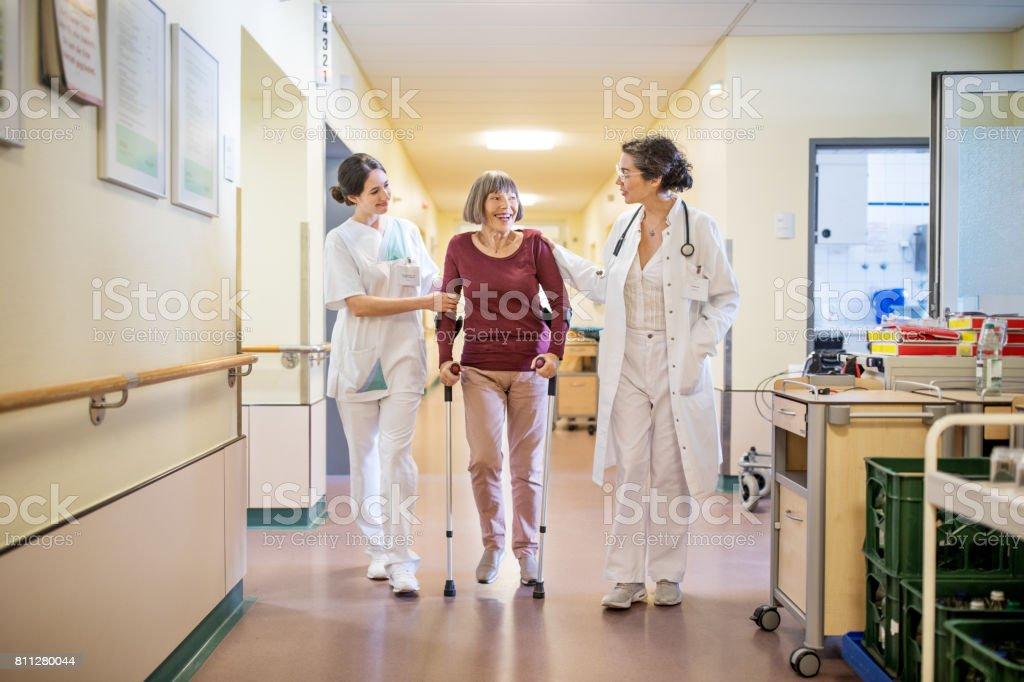 Ältere Frau mit Gehstock von Arzt und Krankenschwester geholfen - Lizenzfrei 70-79 Jahre Stock-Foto