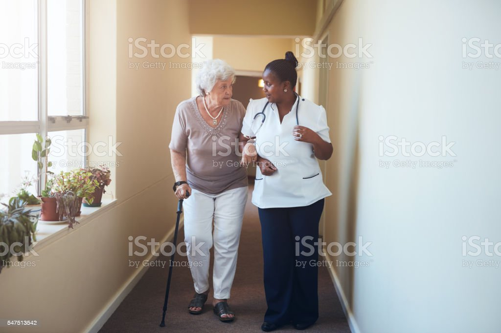 Senior woman with walking stick being helped stock photo