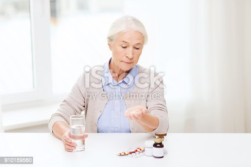istock senior woman with water and medicine at home 910159580