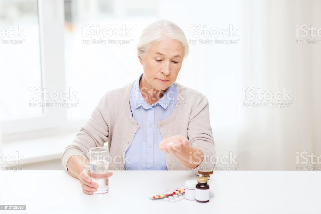 senior woman with water and medicine at home stock photo