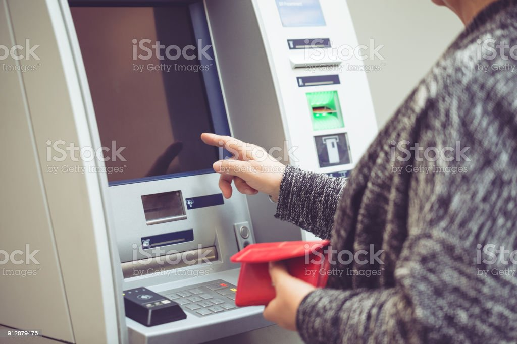 Senior woman withdrawing money from ATM stock photo