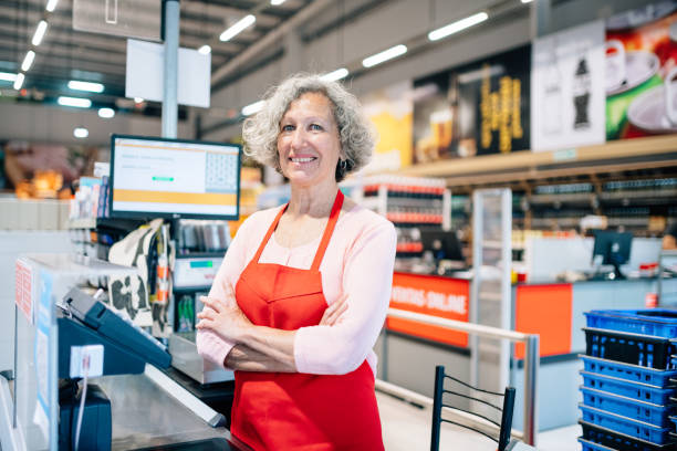Senior woman working as cashier in supermarket stock photo