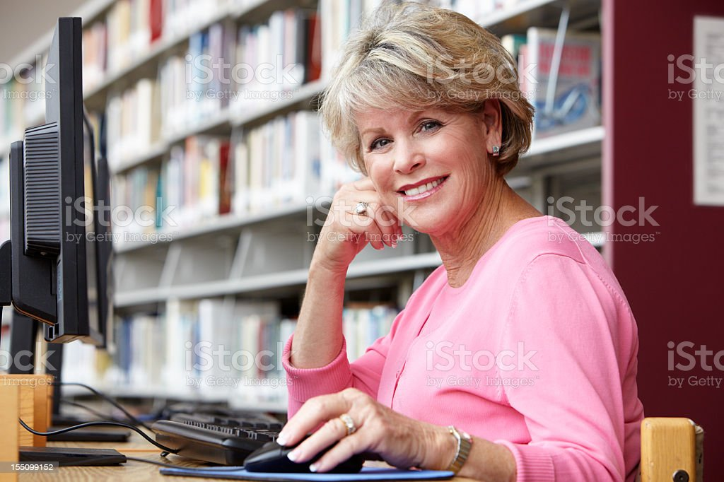Senior woman working on computer in library royalty-free stock photo