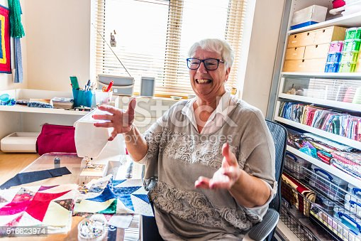 Senior woman enjoying working on her hobby of quilting in her sewing room at home