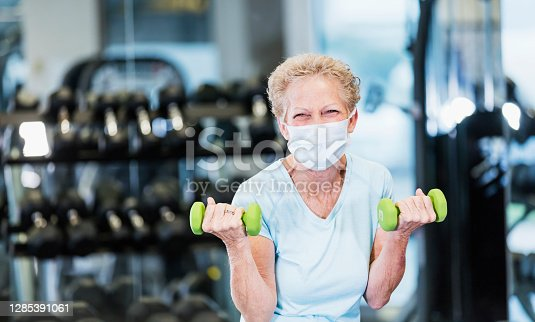 A senior woman in her 60s working out at the gym, lifting hand weights. She is exercising during the covid-19 pandemic, wearing a protective face mask to prevent the spread of coronavirus.