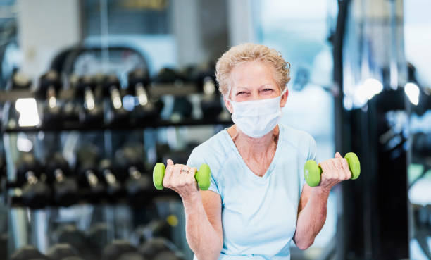 Senior woman working out at the gym, wearing face mask stock photo