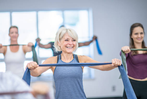 Senior woman working out A senior woman is using an exercise band in a fitness class. There are women around her with fitness bands as well. They are indoors. exercise class stock pictures, royalty-free photos & images