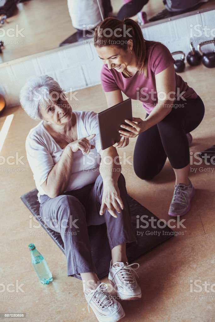 Senior woman workout in rehabilitation center. Personal trainer showing something  on digital tablet. Looking at camera. stock photo