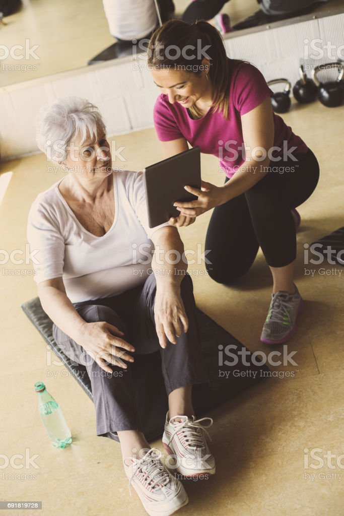 Senior woman workout in rehabilitation center. Personal trainer showing something  on digital tablet. stock photo