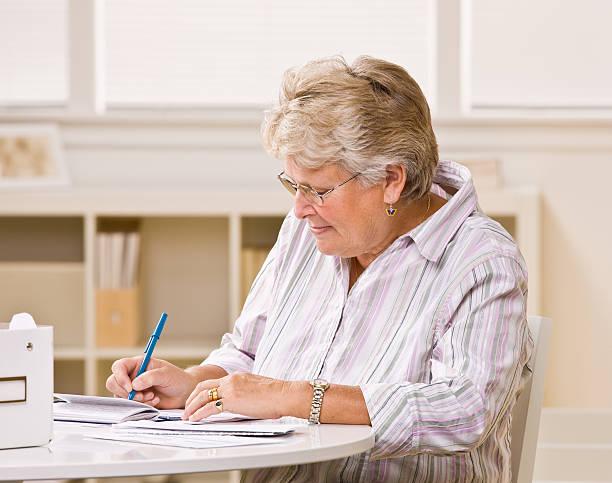 Senior woman writing checks stock photo