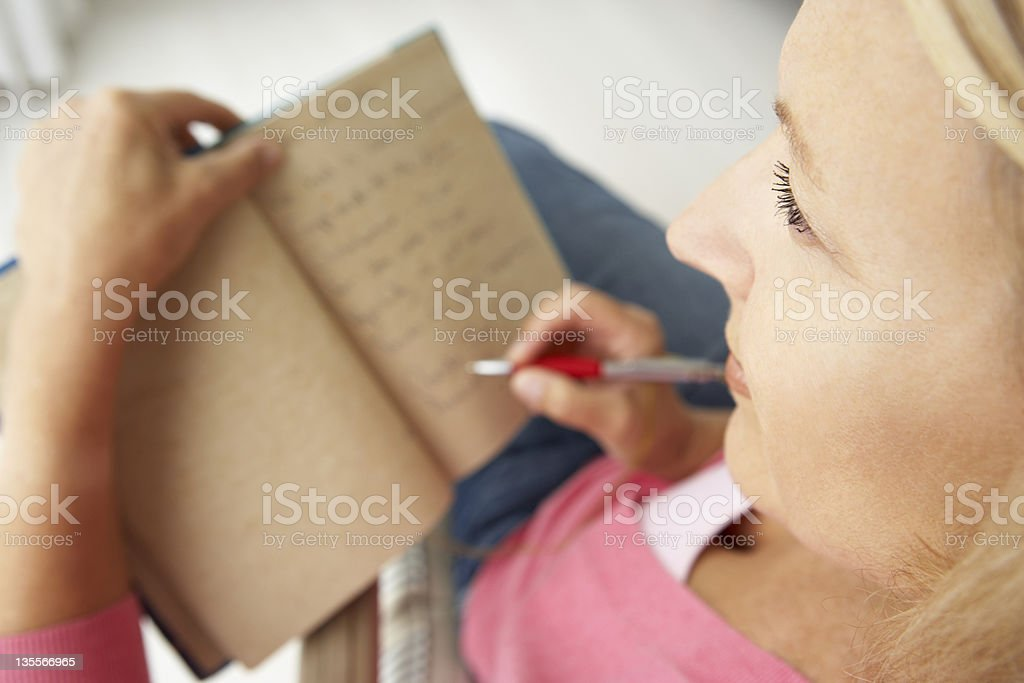 Senior woman writing in notebook stock photo