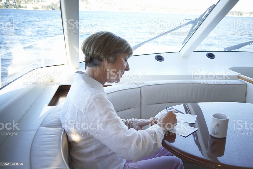 Senior woman writing postcards at table on yacht stock photo
