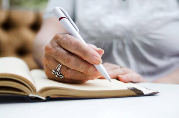 старшая женщина, пишущая карандашом на открытой записке. - писать стоковые фото и изображения