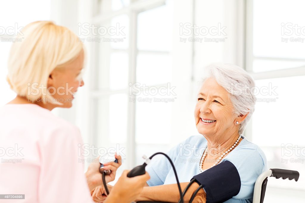 Senior Woman's Blood Pressure Being Examined By Nurse royalty-free stock photo