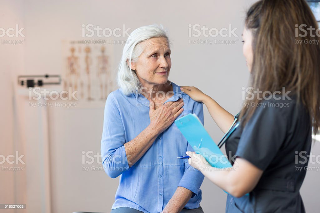 Senior Woman's Doctor's Office Visit For Chest Pain stock photo
