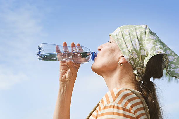 Senior womans drinks water from bottle stock photo