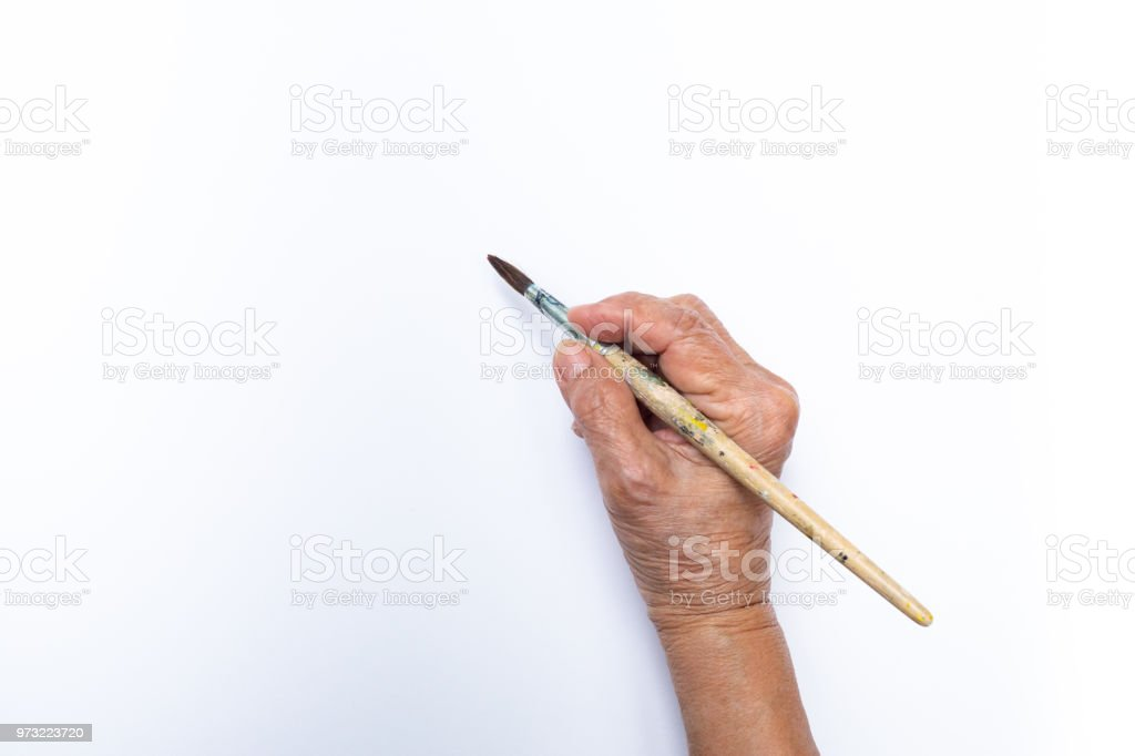 Senior woman's hand painting with paintbrush isolated on white background stock photo