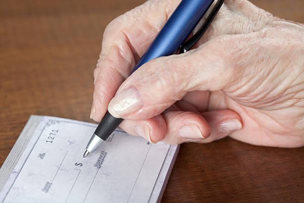 senior woman's hand writing bank check stock photo