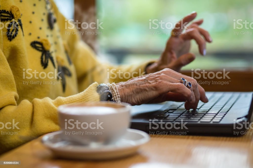 Senior woman's hands and keyboard. stock photo