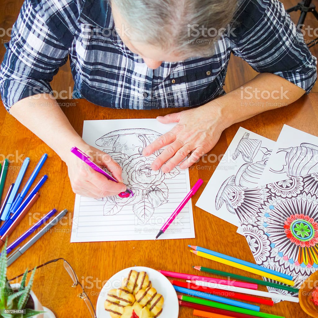 Senior Woman's Hands Holding a Pink Marker Coloring Flowers stock photo