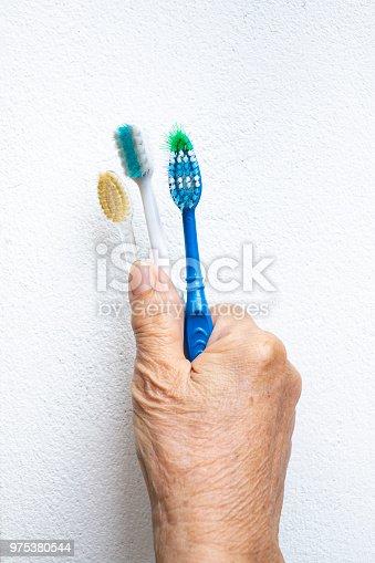 istock Manos de mujer Senior con tres cepillos de dientes viejos fondo  blanco 975380544 7e74ee881bf2