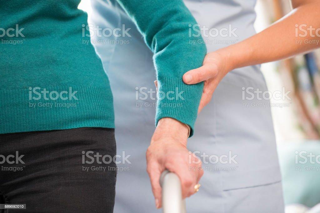 Senior Frauenhand auf Rahmen mit Pflegedienst im Hintergrund laufen – Foto