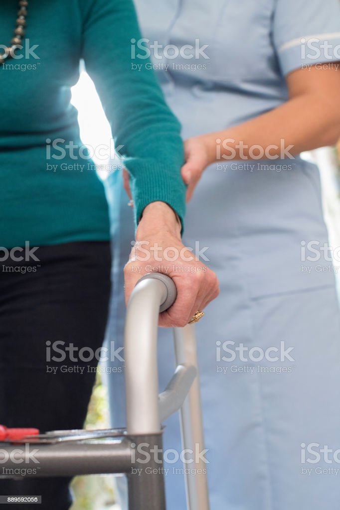 Senior Woman's Hands On Walking Frame With Care Worker In Background stock photo