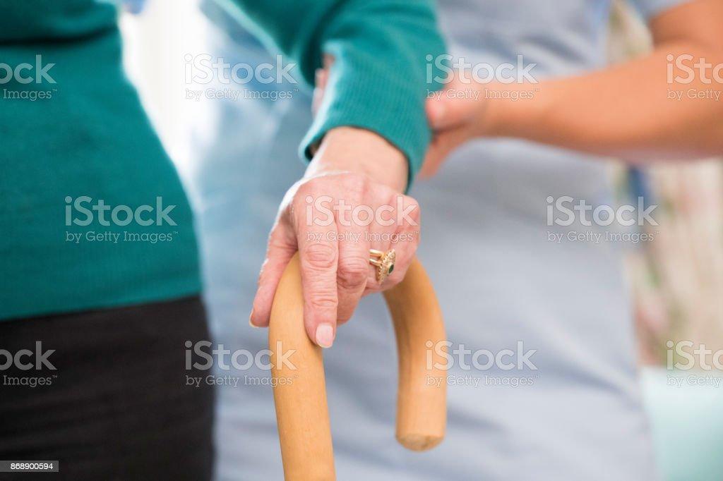 Manos de Senior mujer en el bastón con cuidado del trabajador en el fondo - foto de stock