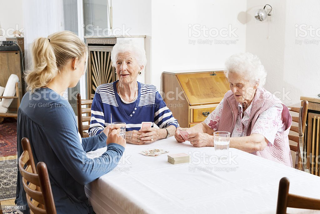 senior women and caregiver playing cards royalty-free stock photo