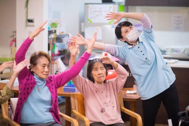 年配の女性と女性看護師のストレッチ - 高齢者介護 ストックフォトと画像