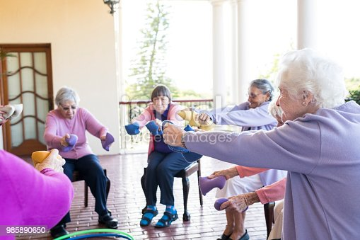 1047537292 istock photo Senior women at exercise class holding weighted bags with arms outstretched 985890650