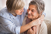 Two senior women at home, hugging. Family and generations concept.