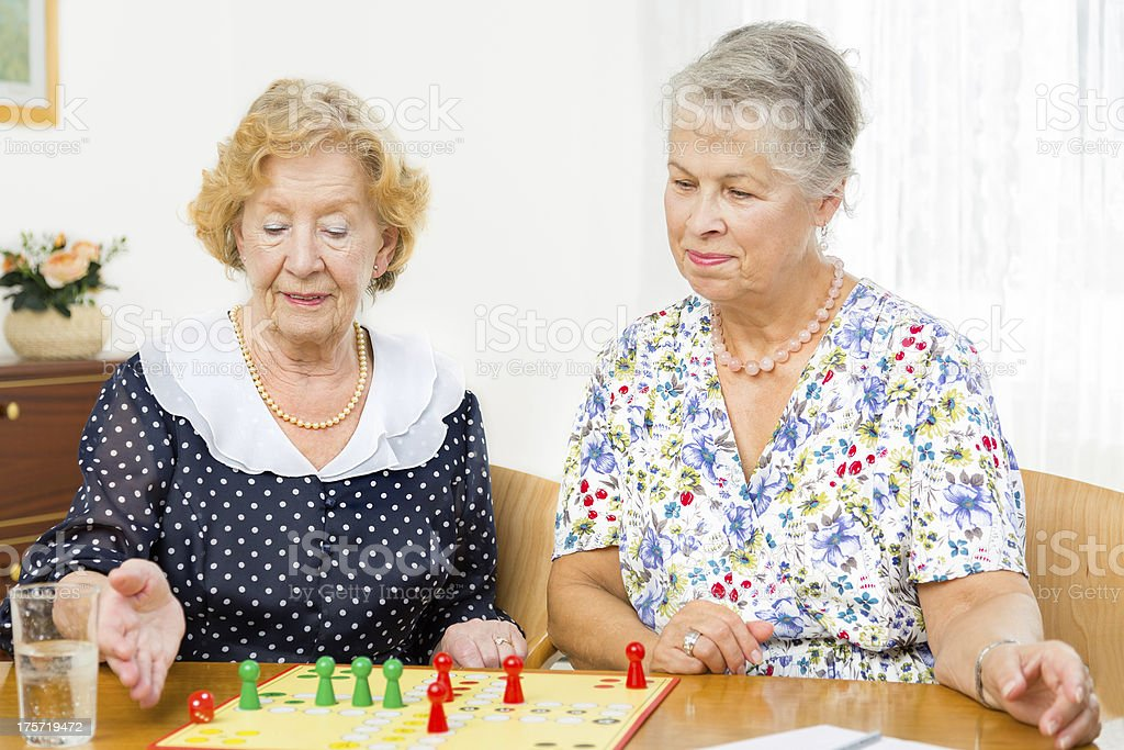 Senior women couple playing board game ludo royalty-free stock photo
