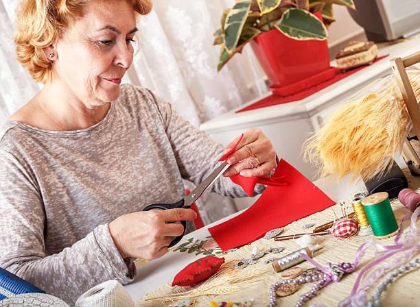 senior damen cuting rot stoff mit schere - altes schmuckkunsthandwerk stock-fotos und bilder