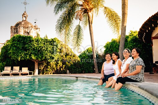 Senior Women dipping feet in Hotel Swimming pool