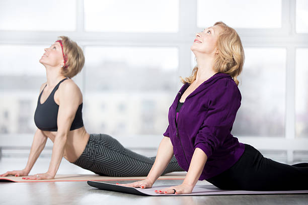 Senior women doing Cobra pose Fitness, stretching practice, group of two attractive smiling fit mature women in sportswear working out in sports club, doing Cobra posture, backbend exercise, bhudjangasana (Bhujangasana) in class cobra pose stock pictures, royalty-free photos & images