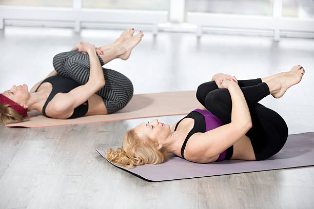 """Senior women doing Knees to Chest Pose Fitness, stretching practice, group of two attractive fit mature women working out in sports club, """"warming up"""", doing Knees to Chest Pose in class, therapeutic for low back, full length apanasana stock pictures, royalty-free photos & images"""