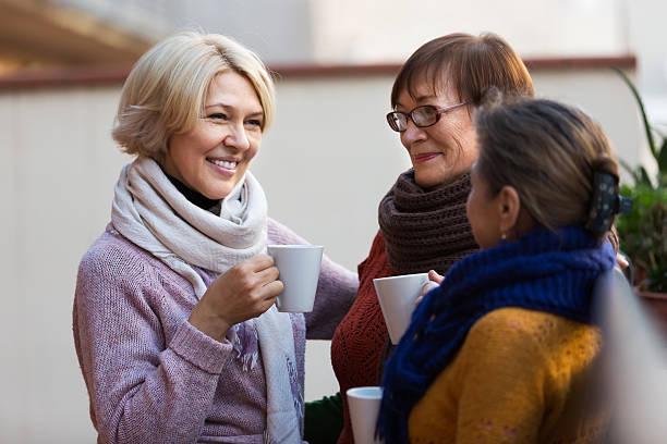 senior donna bere tè con balcone - vicino foto e immagini stock