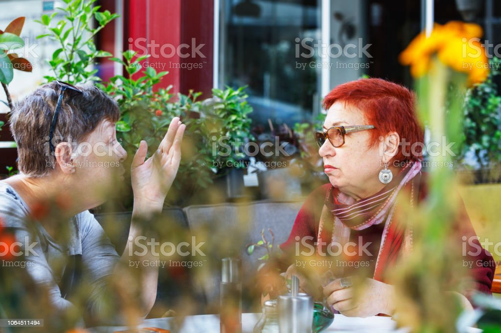 Senior women enjoy discussion at sidewalk cafe table stock photo